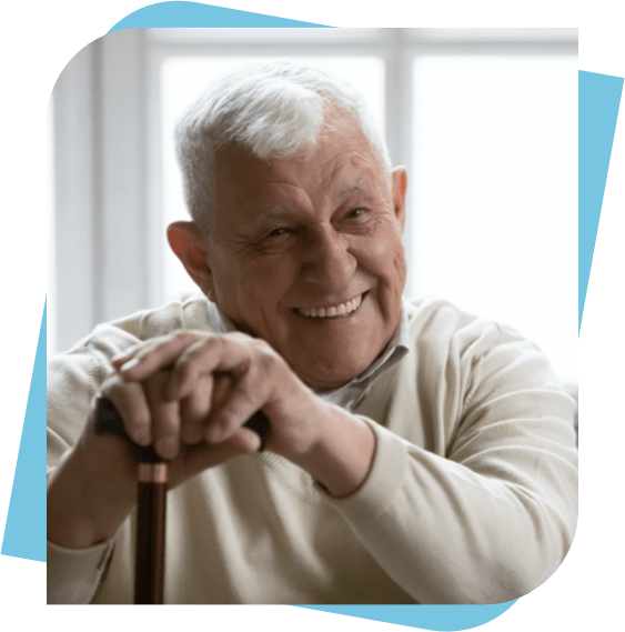 Elderly man smiling while holding his cane.